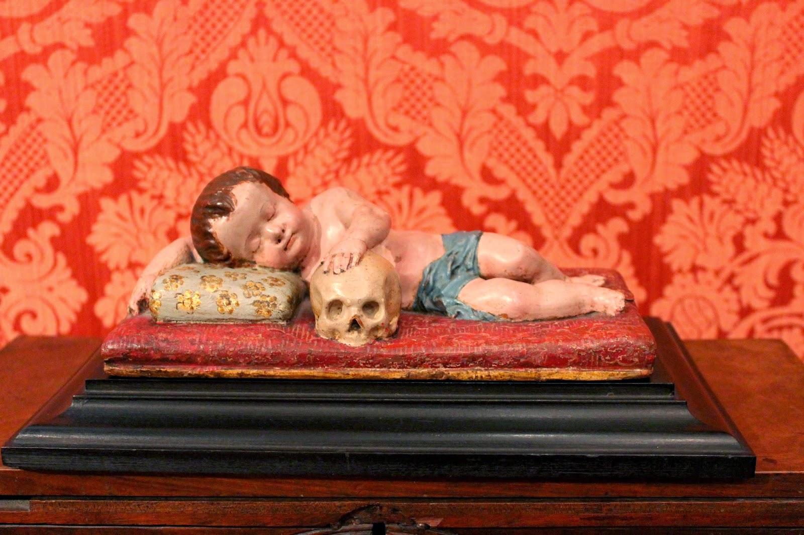 Talla de madera de niño con calavera en el museo del Romanticismo