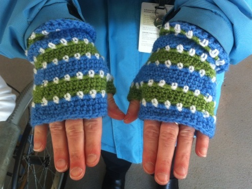 Lisa's hands (palms facing downwards) modelling fingerless mitts in horizontal stripes in Adelaide Oval colours. Solid stripes in mid blue and mid lime green are separated by horizontal rows of white dots.