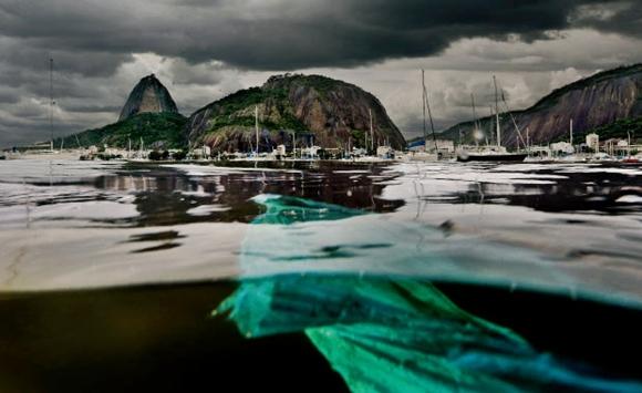 Um pedaço de plástico boia na água marrom da Enseada de Botafogo: vergonha em um dos lugares mais bonitos do mundo. Crédito: Rodrigo Thome