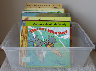collection of picture books in a plastic bin