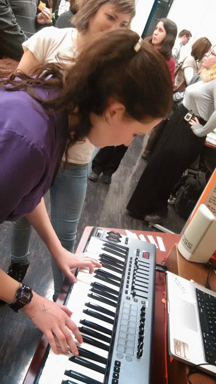Photo of a woman playing a keyboard in a crowded room.