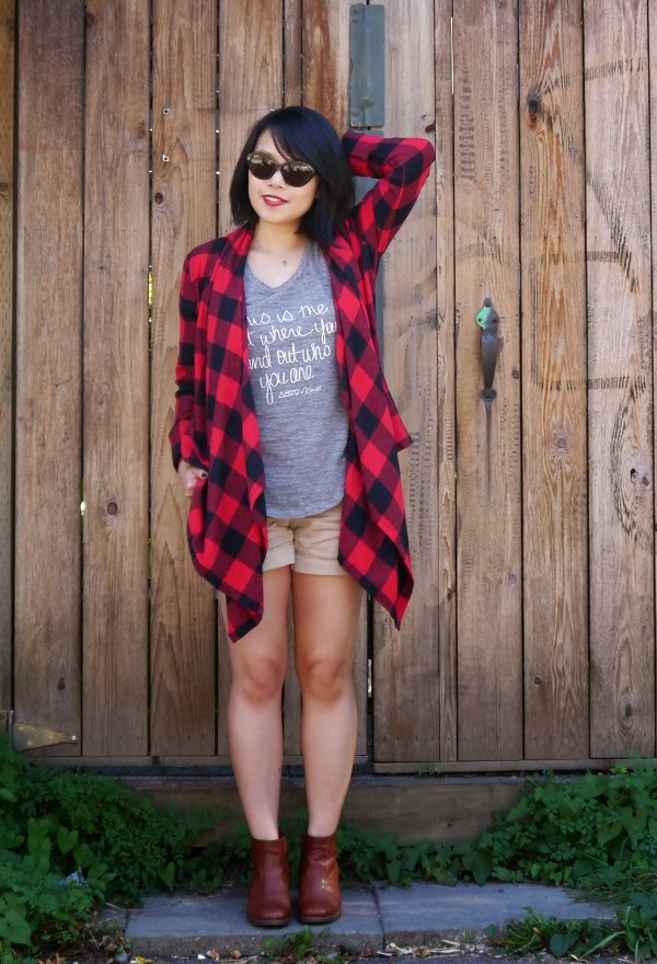 Summer to fall transitional dressing: buffalo plaid wrap, heather grey tank, khaki shorts, cognac ankle boots, and cat-eye sunnies