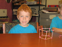 Student showing a pentagonal prism made from toothpicks