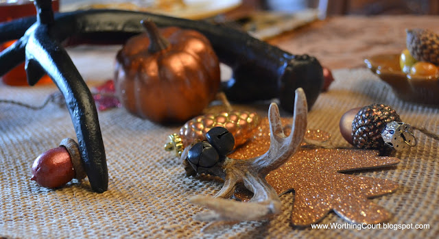 antlers, painted acorns and painted faux pumpkins on a burlap runner for Thanksgiving via Worthing Court blog