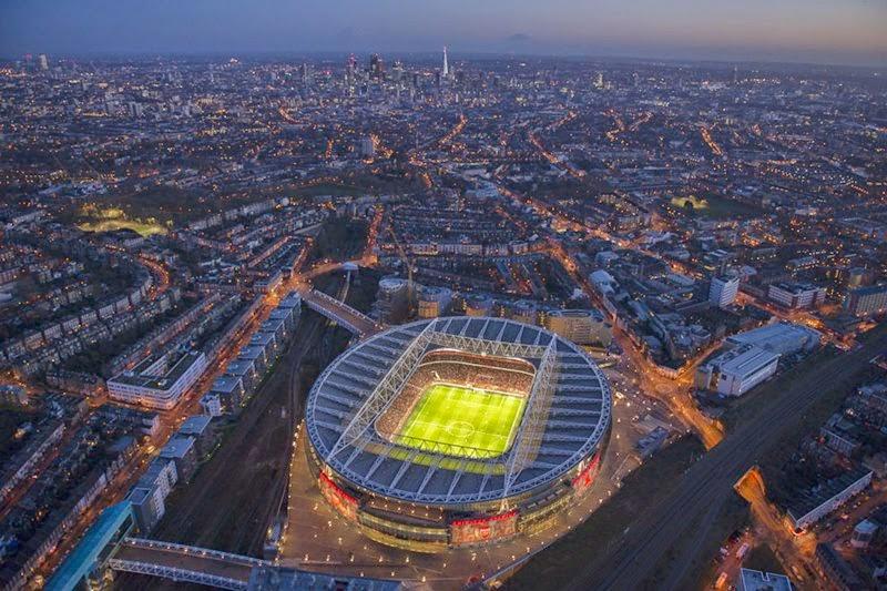 An illuminated Emirates Stadium at night during a match between Arsenal and Crystal Palace, London.