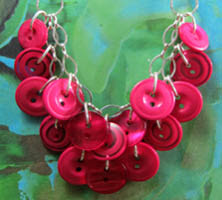 Necklace has layers of plunging pink buttons, each hanging from long silver loops