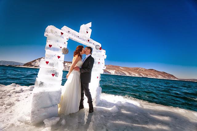 жених и невеста целуютс под свадебной аркой