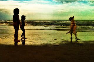 Duas meninas brincam com uma cadela labrador na beira da praia.