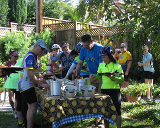 Cyclists loading their plates with the main course in a shady backyard.