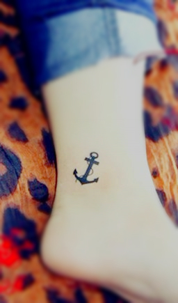 A small anchor tattoo on the ankle saying refuse to sink