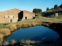 La masia de Ca l'Agustí amb la seva bassa a primer terme