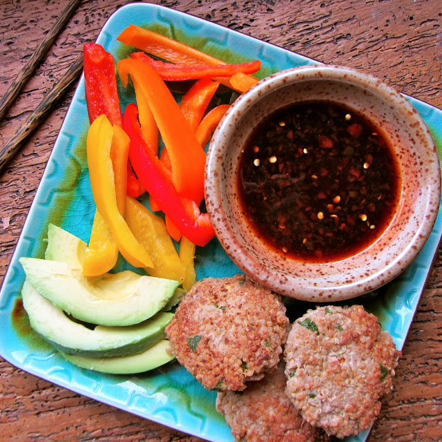 Blue plate with 3 cooked sliders with raw sliced red, orange, and yellow peppers and avocado.