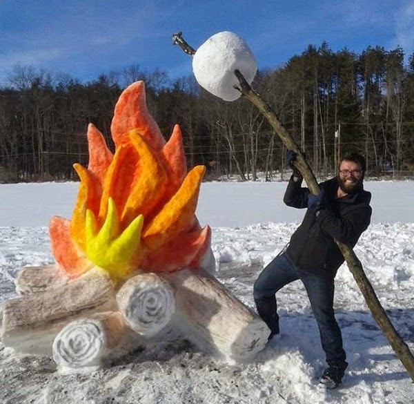 Here's Schaffer roasting a faux (or snow) marshmallow over the fire. - These Artists Made A Roaring Campfire Out Of Freshly Fallen Snow
