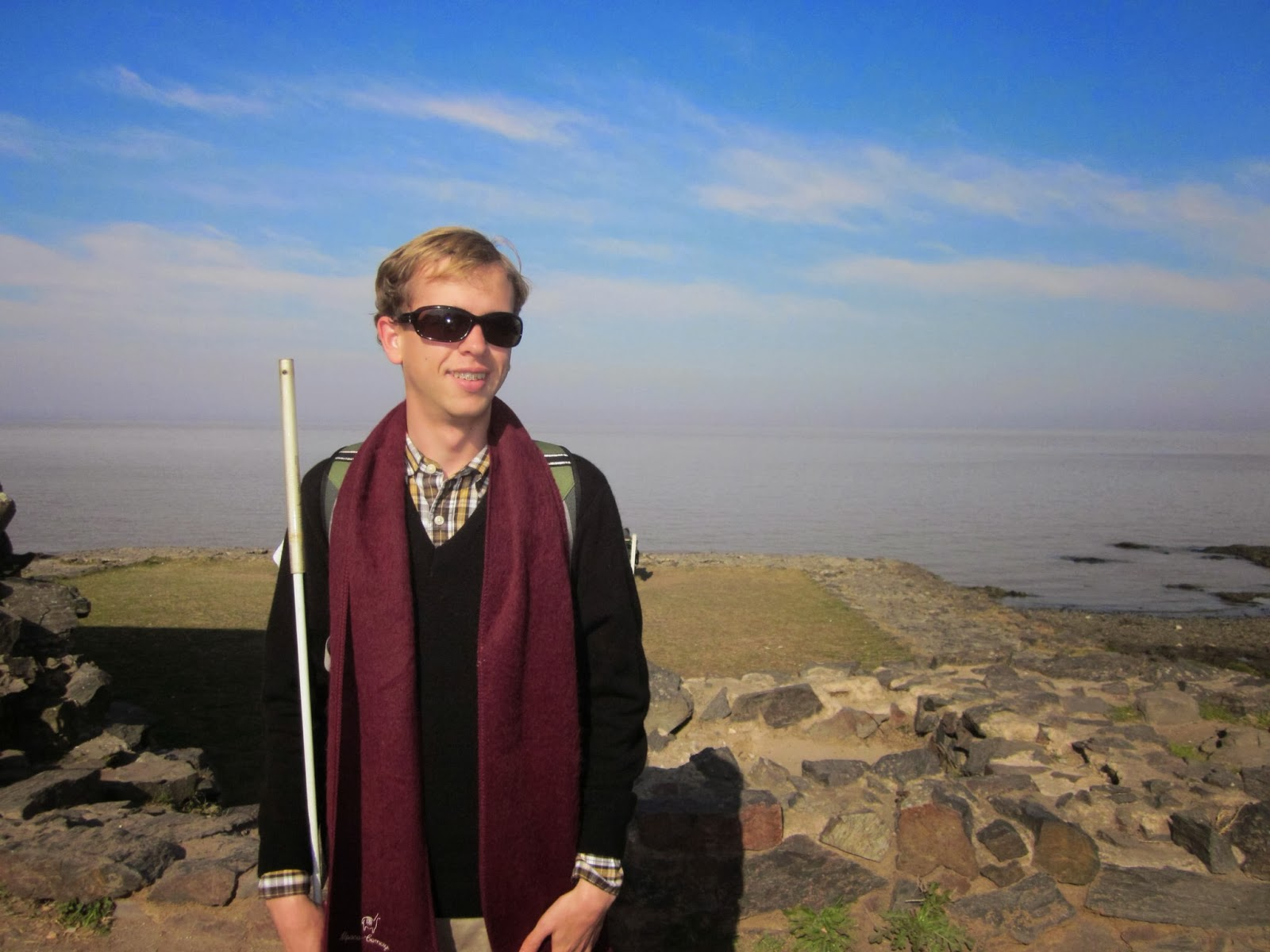 Picture of Justin, young blond man smiling and wearing sunglasses and a scarf and holding his white can at his side standing in front of a rocky beach with the coastline in the background