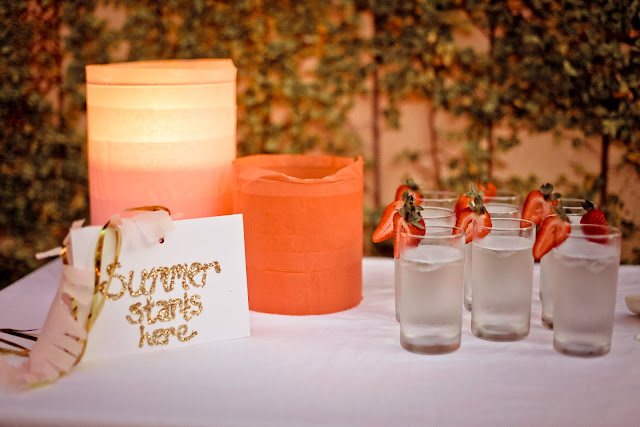"table with glasses of water with fresh strawberries on the rim, orange lanterns and a sign that says ""Summer Starts Here"""