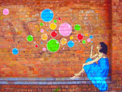 public art brick wall painting of a girl blowing coloured bubbles