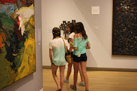 Three young ladies enjoy the abstract art wandering through the gallery.