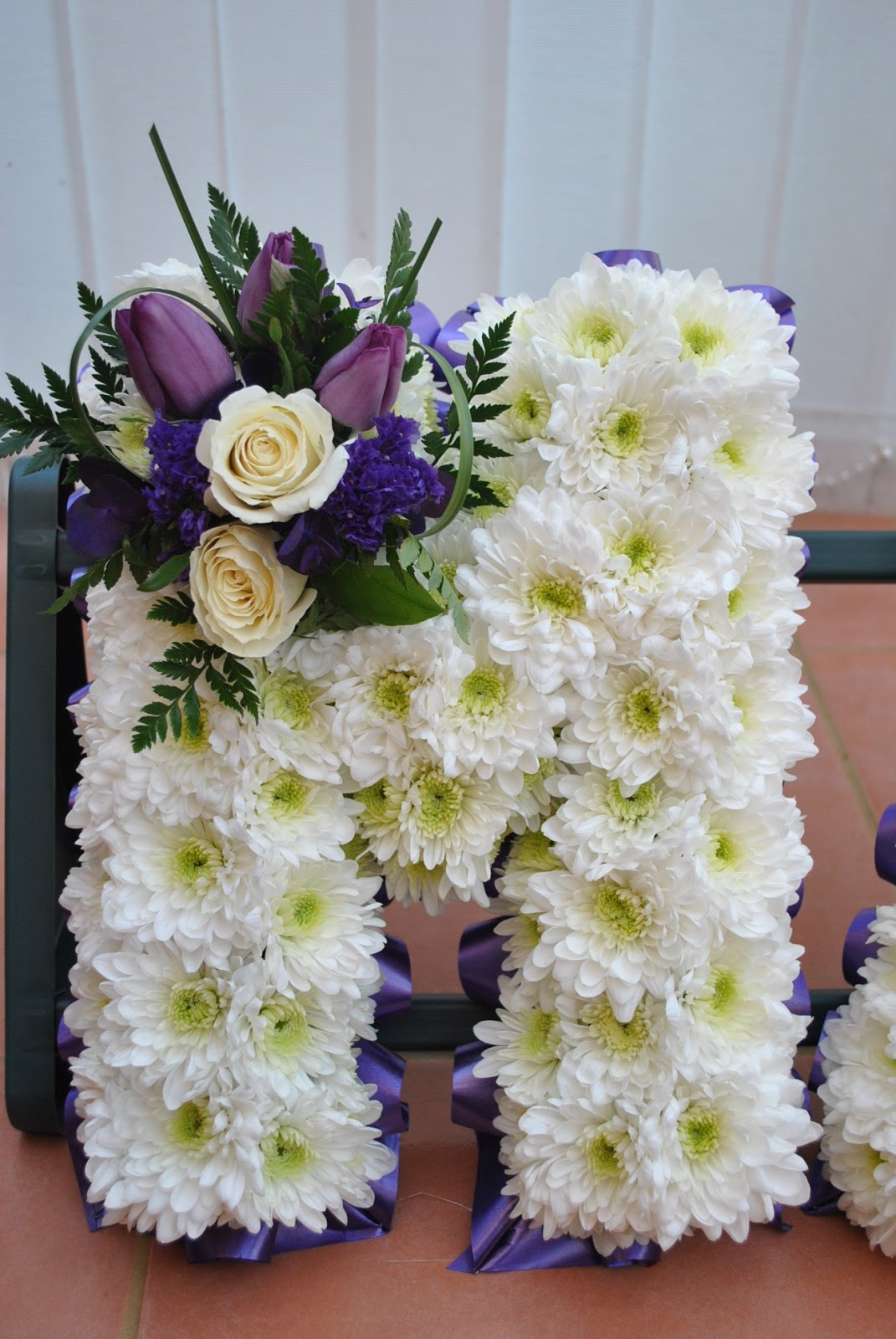 Lucys flower studio matts funeral flowers matts funeral flowers letters in white and purple izmirmasajfo Images