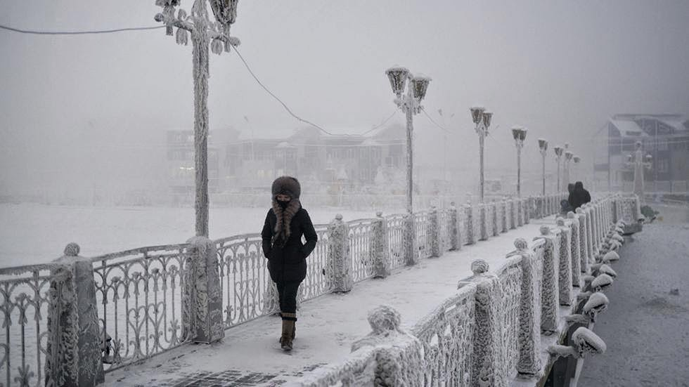 A woman walks over an ice-encrusted bridge in Yakutsk. Oymyakon lies a two day drive from the city of Yakutsk, the regional capital. - Welcome to The Coldest Place Inhabited By Humans on Earth