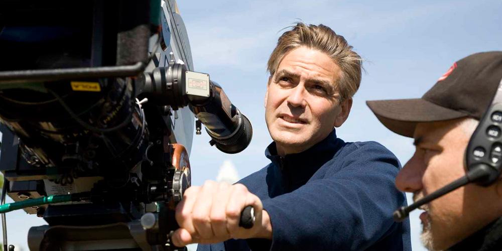 george clooney, como diretor, no set de filmagem de ER: palntão médico, segurando uma câmera cinematográfica junto com um homem de sua equipe
