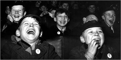 black and white photo of children laughing at a movie theater