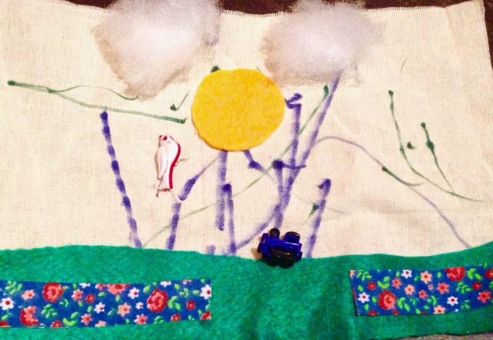 Descrição da foto: Composição de um trabalho feito no educativo voltado para o público infantil. Sobre um tecido bege, traços azul e verde no fundo, duas nuvens feitas de malha acrílica, sol amarelo de feltro, pássaro e trem de plástico em miniatura, chão de feltro verde com outro tecido florido.