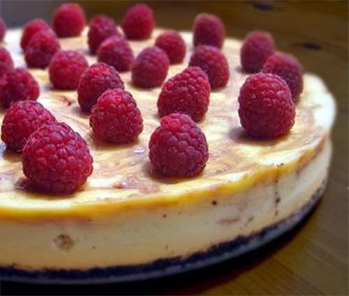 White chocolate cheesecake with raspberry swirls topped with fresh raspberries.