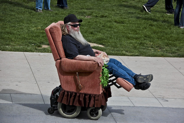 A guy with a big, white beard in a wheelchair with a Lazy Boy recliner as the seat cover.