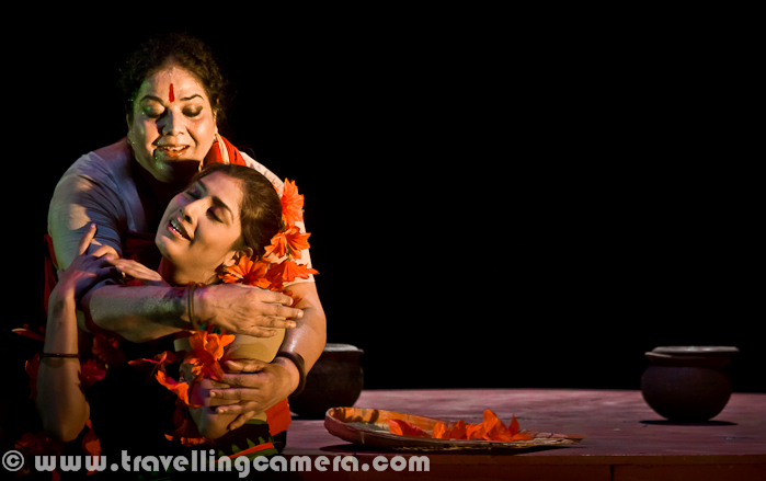 Chandalika was another very famous play of 14th Bharat Rang Mahotsav and it was not very easy to get tickets for the play. This play was performed twice during the festival - Once in Bengali and second time in Hindi. Here is a quick Photo Journey from Chandalika by Usha Ganguli...Tagore's Chandalika tells the tale of Prakriti, an untouchable girl forced to live on the periphery of society as 'chandalika'. No one want to play with her, people keep distance from her but at times increase closeness for their selfish reasons. Chandilika by Tagore is based on a story from a Buddhist text... and here I would like to highlight that 14th Bharat Rang Mahotsav 2012 is also a platform to celebrate Rabindarnath Tagore's 150th Birthday. Many of his plays are being shown during Bharangam 2012 !!!Play starts with some dialogs by Usha Ganguli where she describes the situation of her region without water and how people are crying for water. Usha is playing main role in this play. She has a daughter and both of them are treated badly by higher society. At the same time, she helps the local kingdom by helping in various problems like water scarcity.Here is a photograph of musicians in this play who were also sitting on the stage. There was no recorded music during this play and whole music direction was awesome. I liked the running horse sound the most. The man in the middle created that sound through the big drum in front of him. Girls on the other side sung a beautiful song and they also joined for acting, while one of the monk was moving around the villages to spread right information about caste system and related issues.Here is a photograph showing Prakriti with her mother and when she is requesting her mother for not going to King's place. Her Mother is invited by king to use her magical powers to bring water in the region and make people happy. During the dialog, Prakriti was confident that King will not allow lower cast people to have water and it will be accessible to other v