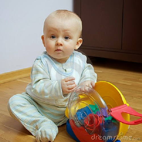 Photo de bébé avec yeux bleus  qui joue