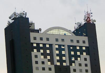 Da imagem anterior nos chamou a atenção o topo deste edifício pós-moderno, com suas platibandas apinhadas de receptores e transmissores de telecomunicações, como se fossem ervas daninhas sobre as ruínas de uma era analógica.
