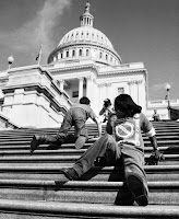 Photograph of people with disabilities crawling up the capital steps. The capital is far away in the foreground, showing the inaccessiblity of the Capital for persons with disabilities.