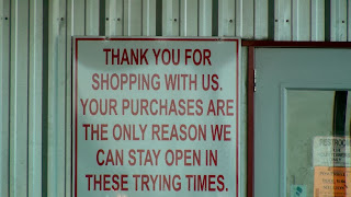 "sign stating ""Than you for shopping with us. Your purchases are the only reason we can stay open in these trying times"""