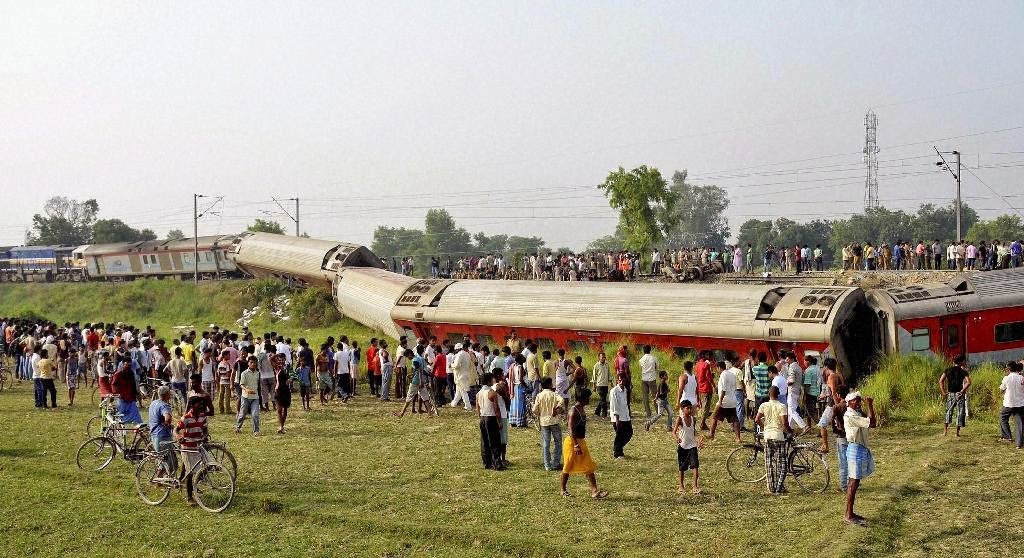 People gather around a passenger train that derailed in Bihar, near Chhapra town, India, Wednesday, June 25, 2014. A passenger train derailed early Wednesday in the eastern Indian state of Bihar, killing at least four people and injuring eight others, officials said. The cause of the accident was not immediately known.