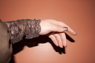 A hand and lower arm in a chocolate brown Victorian-style blouse, showing off a lace cuff and puff sleeve