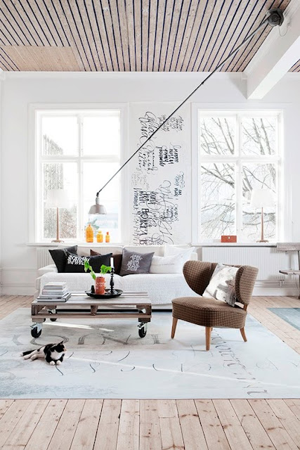 Minimalist white living room with a white sofa, brown armchair, handwritten scribble on a wall, natural wood board ceiling and wood floor