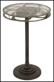The Base Is Crafted From Metal In A Rustic Brown Finish And The Top Is A Movie Film Reel Covered With A Glass Top