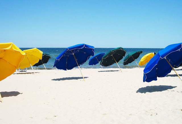 Blue, yellow and green umbrellas on a beach in Nantucket