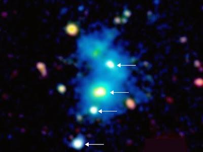 Ένα σπάνιο εύρημα: η περιοχή που περιλαμβάνει το κουαρτέτο των κβάζαρ. Τα 4 κβάζαρ (υποδεικνύονται με τα βέλη) βρίσκονται σε ένα νεφέλωμα – εύρους ενός εκατομμυρίου ετών φωτός – που στην εικόνα φαίνεται με μπλε χρώμα. Το σύστημα αυτό απέχει 10 δισεκατομμύρια έτη φωτός από τη Γη