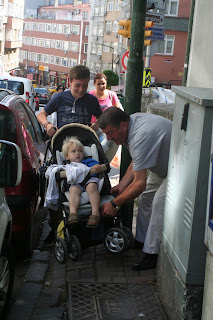 Man helping Ruskin with pushchair.