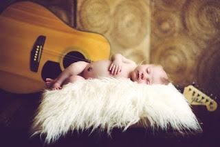 Wallpaper gambar bayi tidur di samping gitar
