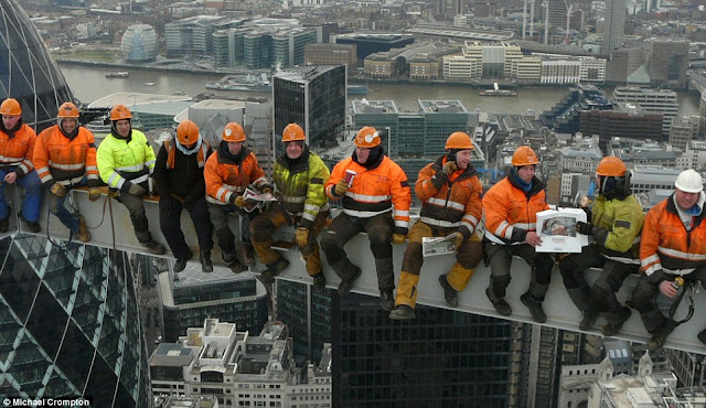 Eleven workers wearing helmets and sitting on the beam on the skyscraper in central London