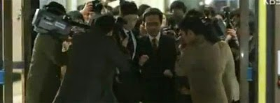 Uhm Hyo Sup 엄효섭 as Kang Sung Wook, surrounded by reporters as he leaves the hospital.