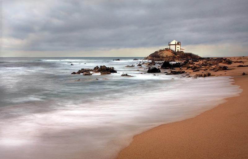 Foto da capela do Senhos da Pedra com o mar calmo embora as ondas a esprariarem longamente na areia. Rochas em roda practicamente descobertas
