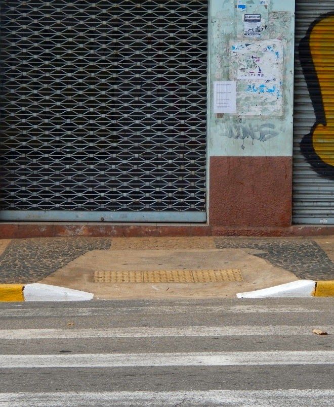 Nesta intervenção feita numa calçada de Paulínia, a intenção foi boa: instalar uma rampa para cadeirantes ao final da faixa de pedestres. A execução, no entanto, teve um resultado inócuo, pois a largura resultante entre a mesma e a edificação, não permite uma manobra de 90 graus em nível para o portador de necessidades especiais. O correto seria aumentar o perfil da calçada na extensão da travessia, uma vez que nesta área já não é possível estacionar veículos.