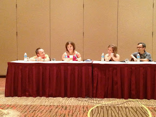 four people sitting at a table participating in a panel discussion at lpa conference