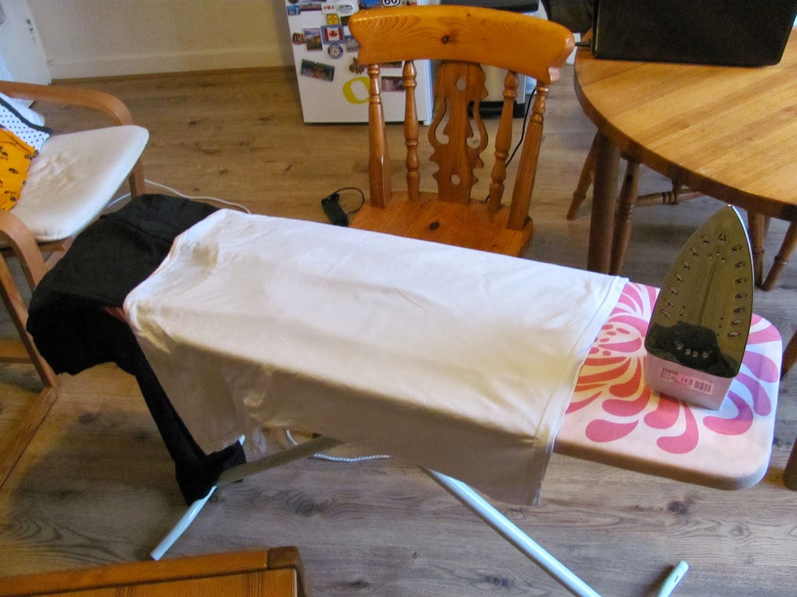 Polyester pants with a damp T-shirt laid over them on an ironing board.