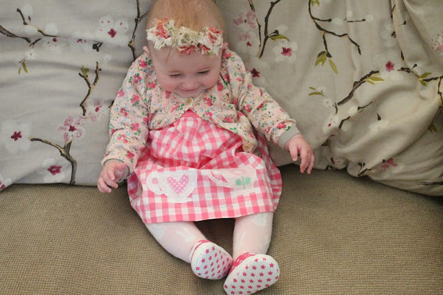 baby wearing pink gingham dress with teacups and floral cardigan & headband