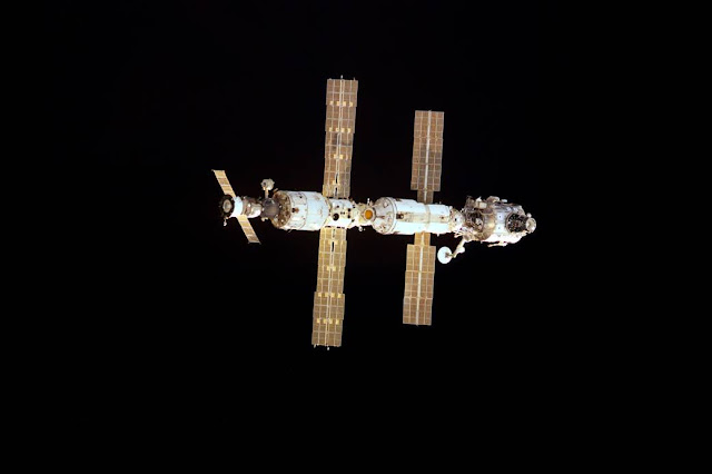 This Dec. 2, 2000, photograph shows the configuration of the space station at the start of Expedition 1 including the Zarya Control Module, Unity Node, Zvezda Service Module and Z1-Truss. It was taken by STS-97 crewmembers aboard shuttle Endeavour during approach to dock with the station on a mission to deliver and connect the first set of U.S.-provided solar arrays, prepare a docking port for arrival of the U.S. Laboratory Destiny and perform additional station assembly tasks. The Expedition 1 crew spent four months living and working on the station and returned to Earth aboard shuttle Discovery on March 21, 2001.