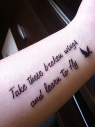 Take these broken wings and learn to fly quote tattoo on arm with bird